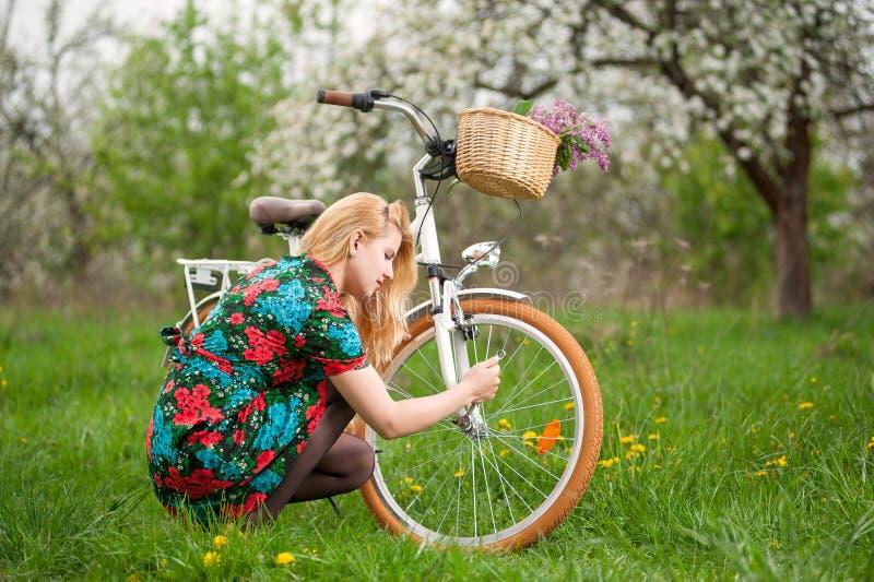 有葡萄酒白色自行车的女性骑自行车者在春天庭院里 免版税库存图片