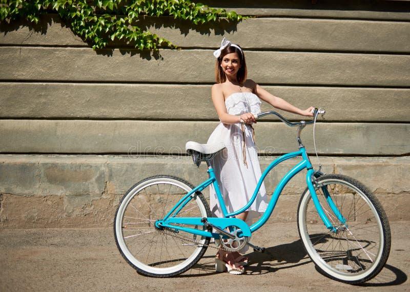 有葡萄酒的微笑的女孩骑自行车看在墙壁背景 免版税库存照片