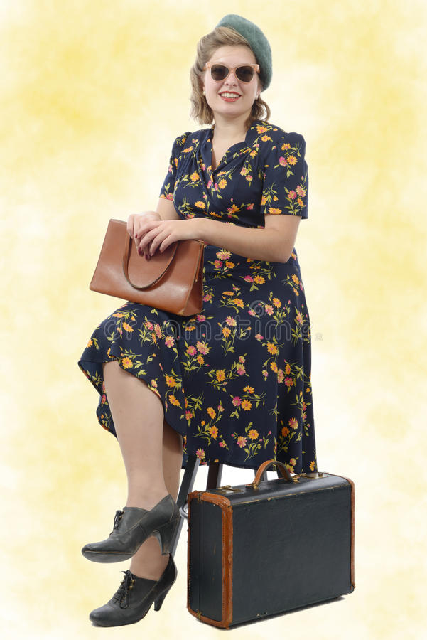 有葡萄酒的美丽的妇女给坐椅子穿衣 库存图片