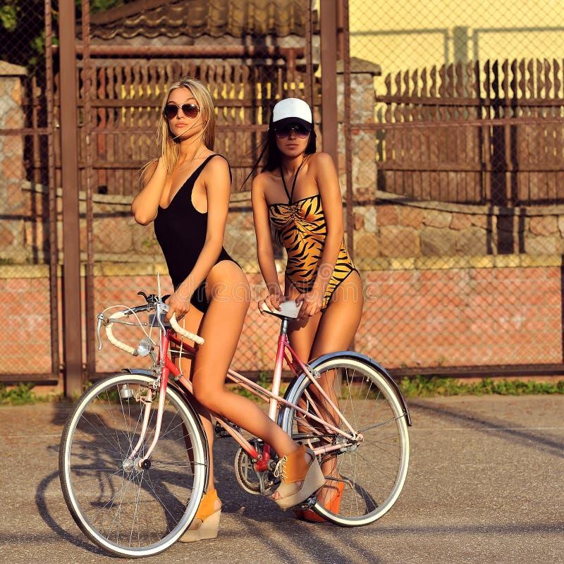 有葡萄酒自行车的两名性感的妇女 方式室外纵向 免版税库存图片