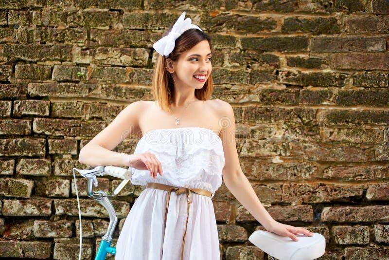 有葡萄酒自行车的特写镜头时髦的女人在砖墙背景 免版税库存照片