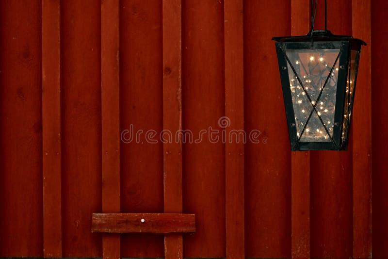 有葡萄酒诗歌选光里面的老葡萄酒灯笼在农村红色木墙壁 圣诞节假期装饰概念 图库摄影