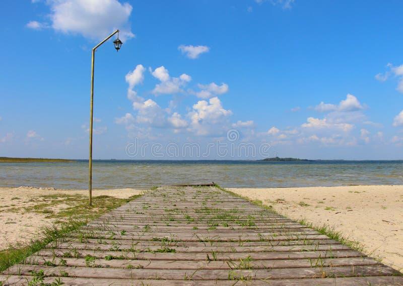 有葡萄酒路灯柱的木老蕨类的码头在反对蓝色夏天天空的湖附近 库存图片