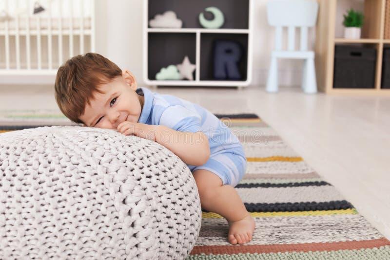 有蒲团的逗人喜爱的婴孩在家 免版税库存照片