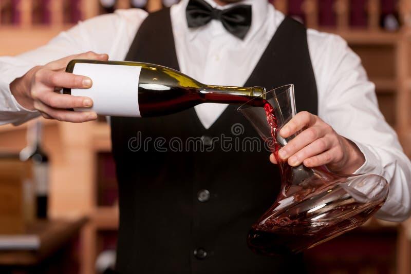 有蒸馏瓶的斟酒服务员。 库存照片