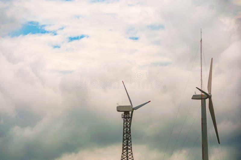 有蓝天和云彩的,风力驻地风轮机 生态能量构成 免版税库存照片
