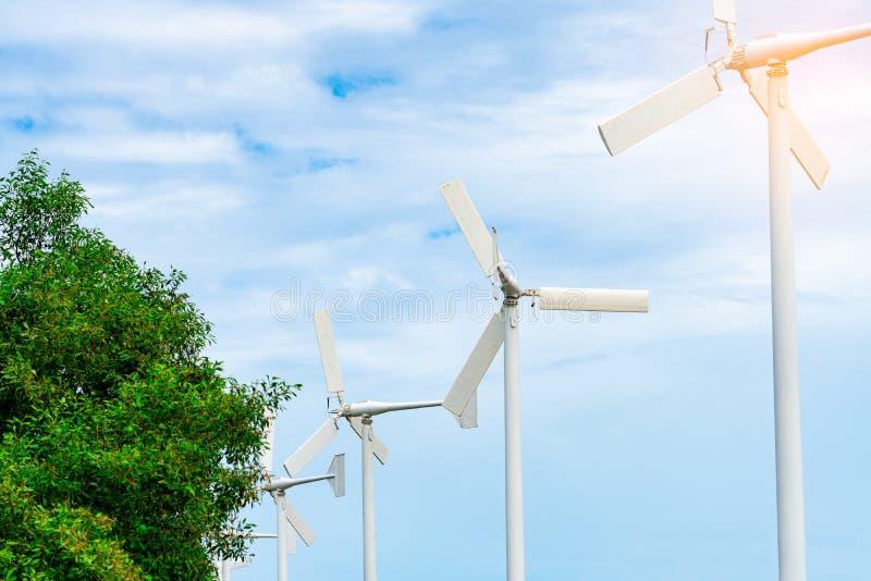 有蓝天的水平的轴风轮机和白色云彩临近绿色树 风能在eco风力场 绿色能量概念 免版税库存图片
