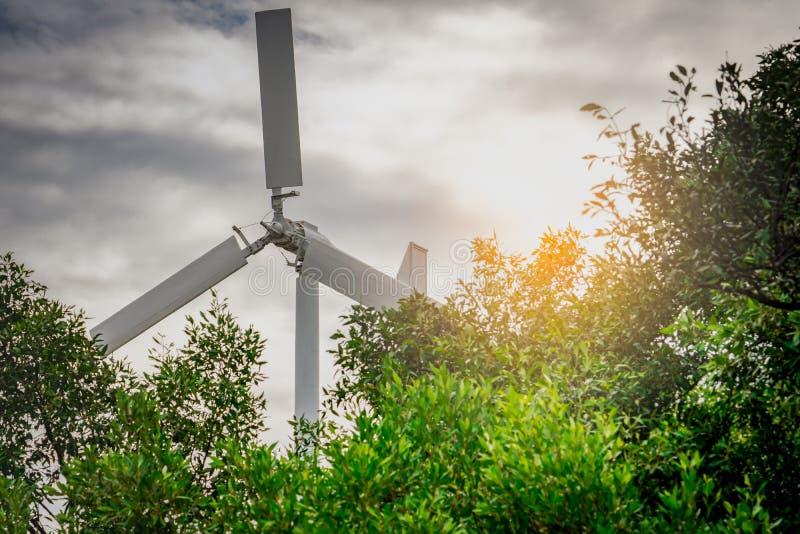 有蓝天的水平的轴风轮机和白色云彩临近绿色树 风能在eco风力场 绿色能量概念 免版税图库摄影