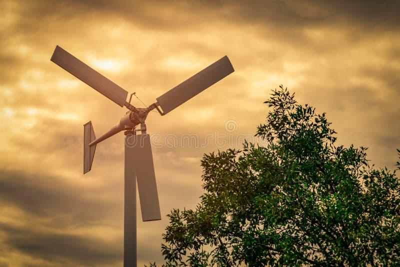 有蓝天的水平的轴风轮机和白色云彩临近绿色树 风能在eco风力场 绿色能量概念 库存照片