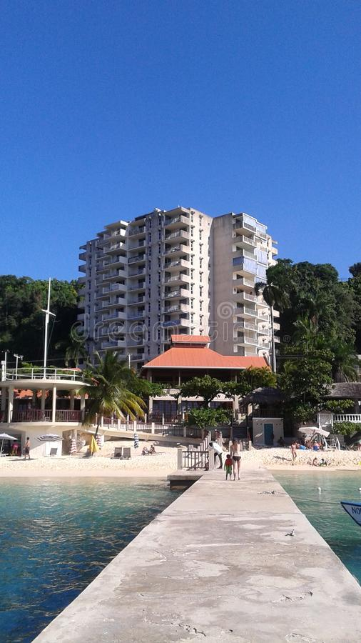 有蓝天的海滩前的公寓房 免版税库存照片