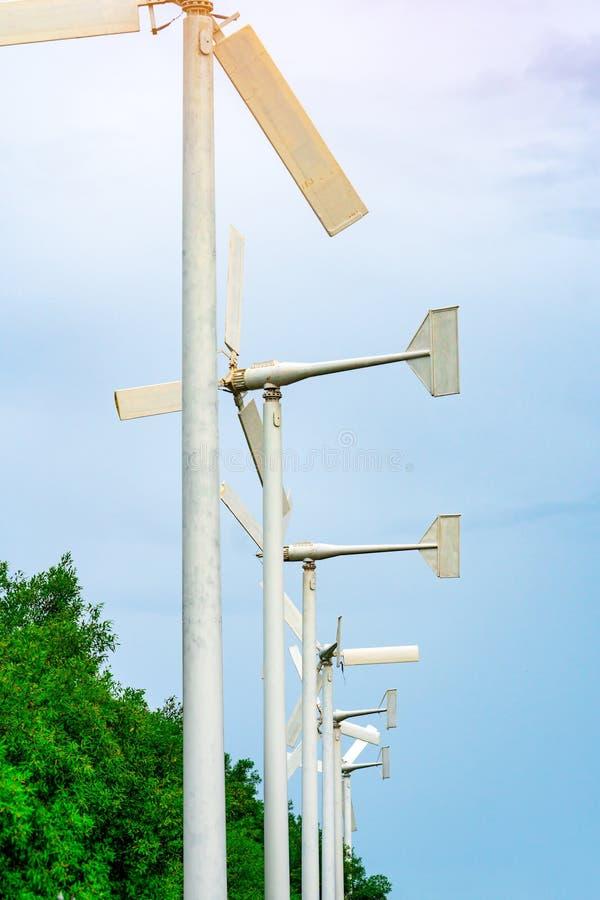 有蓝天的风轮机和白色云彩临近绿色树 风能在eco风力场 绿色能量概念 更新能量 免版税库存图片