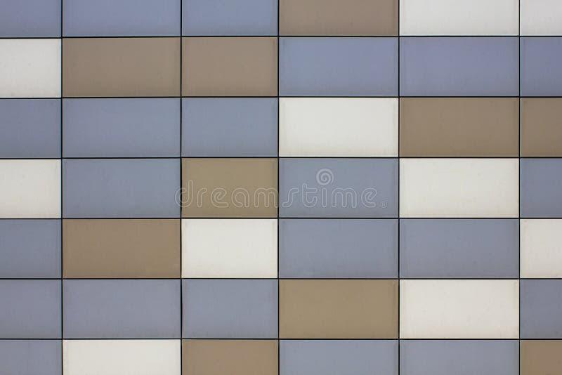 有蓝灰色棕色米黄金属长方形瓦片的墙壁 垂直和水平线 光滑的表面纹理 图库摄影