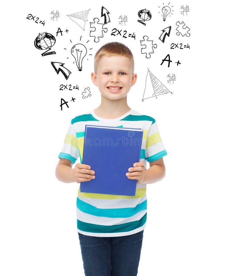 有蓝皮书的微笑的小学生男孩图片