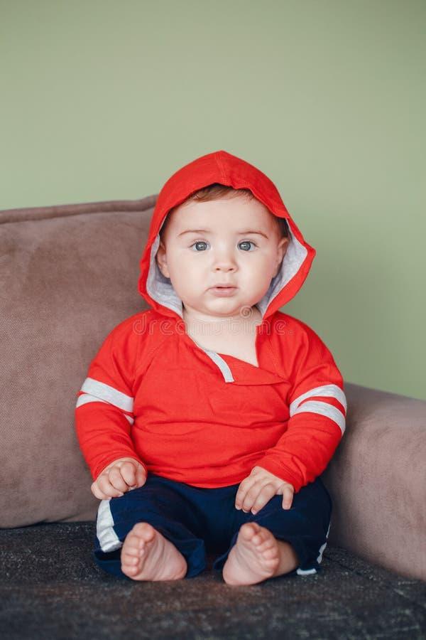 有蓝眼睛、佩带的红色体育有冠乌鸦衬衣和田径服裤子的男婴 库存图片