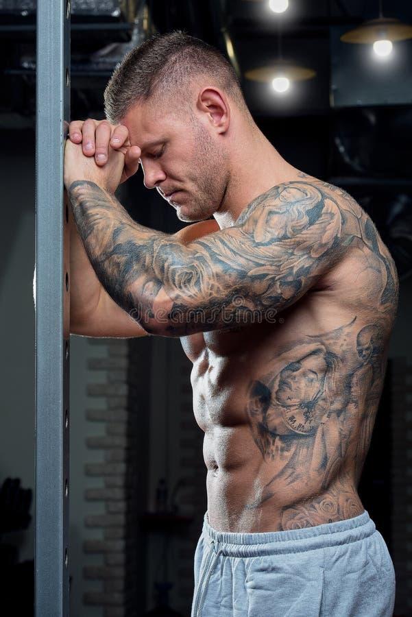 有蓝眼睛和纹身花刺的肌肉赤裸上身的切细的坚强的疲乏的人在灰色裤子的力量笼子摆在健身房 免版税图库摄影