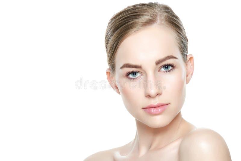 有蓝眼睛和金发的俏丽的女孩,当赤裸肩膀,看照相机微笑 与轻的裸体构成的模型 免版税库存图片