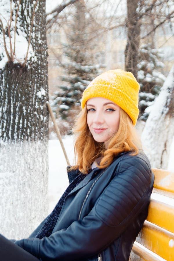 有蓝眼睛和金发的可爱的年轻女人在一黄色编织的帽子和黑皮夹克坐一条黄色长凳 免版税库存图片