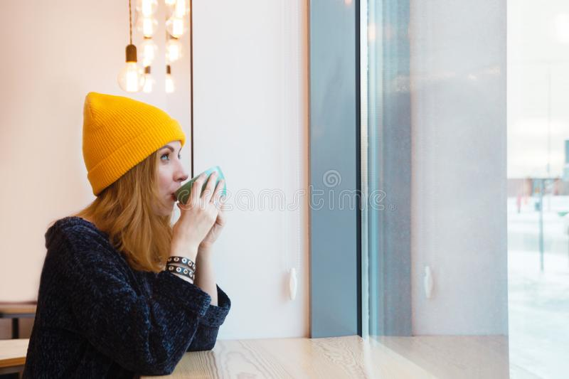 有蓝眼睛和金发的年轻女人在一个黄色帽子喝在咖啡馆的咖啡并且调查窗口 免版税图库摄影