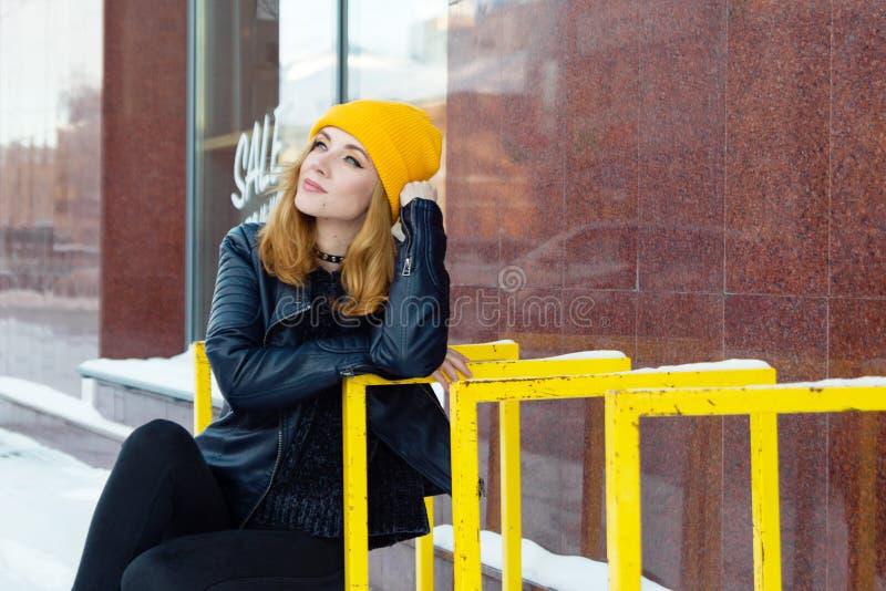 有蓝眼睛和金发的年轻女人在一黄色编织的帽子和黑皮夹克在城市多雪的街道上  免版税图库摄影