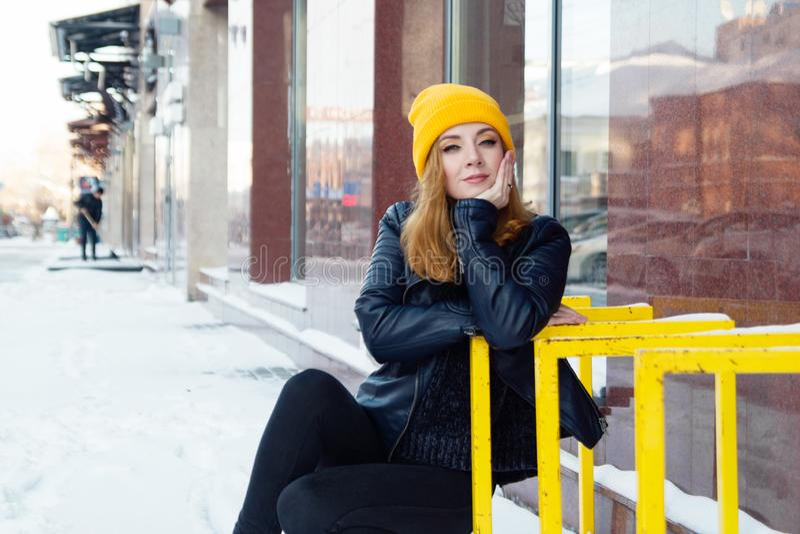 有蓝眼睛和金发的年轻女人在一黄色编织的帽子和黑皮夹克在城市多雪的街道上  免版税库存照片