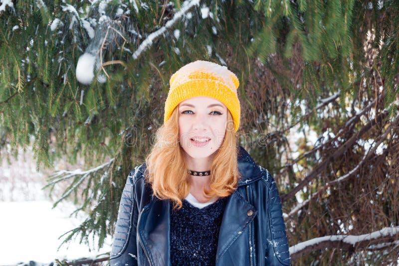 有蓝眼睛和金发的年轻女人在一黄色编织的帽子和黑皮夹克在杉树下 免版税库存图片