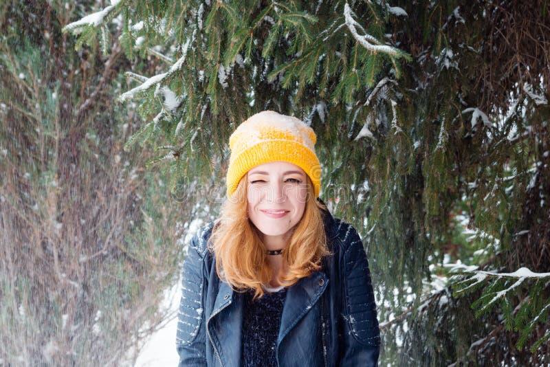 有蓝眼睛和金发的年轻女人在一黄色编织的帽子和黑皮夹克在杉树下 库存照片