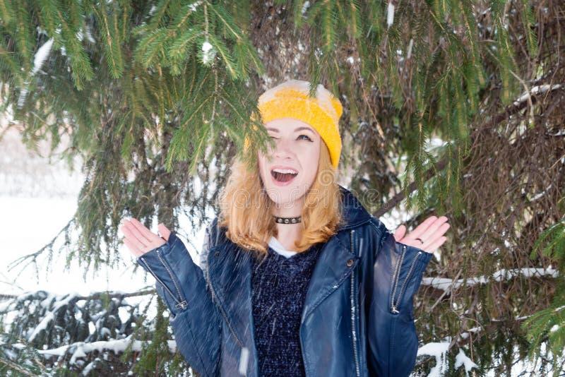 有蓝眼睛和金发的年轻微笑的妇女在一黄色编织的帽子和黑皮夹克在杉树下 免版税库存照片