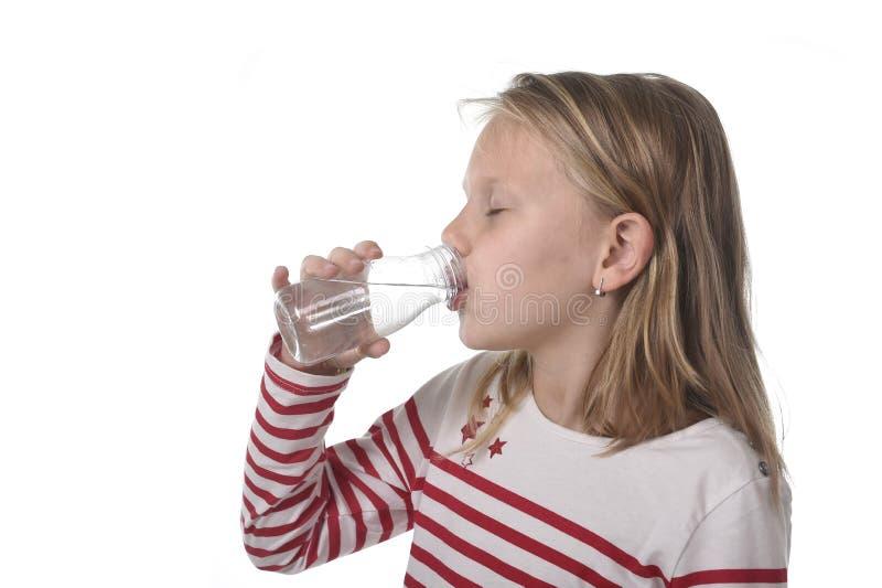 有蓝眼睛和金发的逗人喜爱的甜小女孩举行瓶水喝的7岁 免版税库存图片