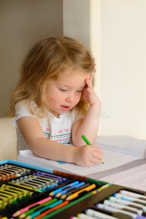 有蓝眼睛的一个逗人喜爱的矮小的白种人白肤金发的婴孩与耳机坐椅子并且今后看 免版税库存照片