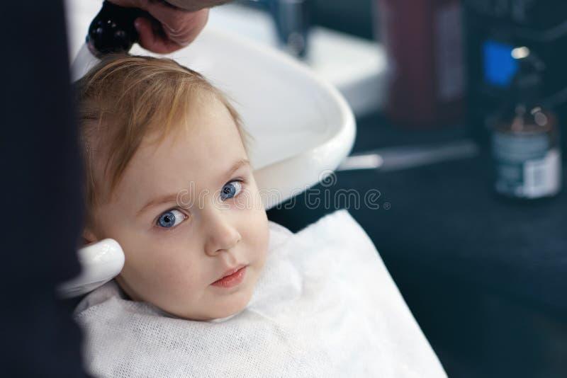 有蓝眼睛的严肃和一点害怕的逗人喜爱的白肤金发的男婴在理发店有洗涤的头由美发师 库存图片