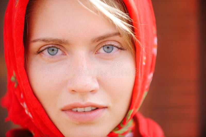 有蓝眼睛的俄国金发碧眼的女人在一块红色方巾在农场工作 女性秀丽和完美的概念 免版税库存照片
