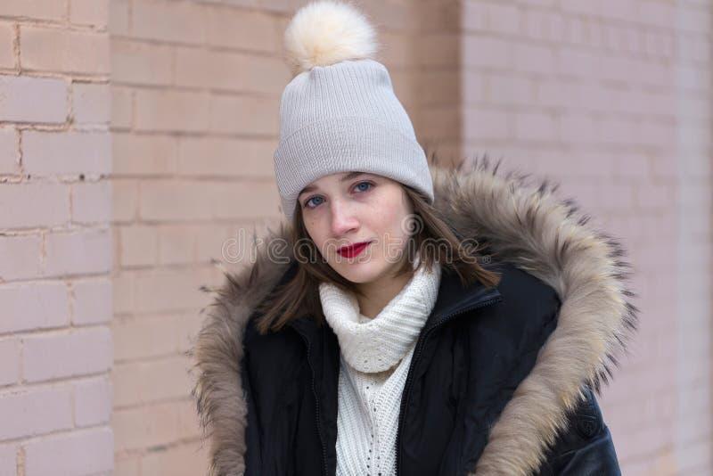 有蓝眼睛的年轻女人和在温暖的冬天外套下的红色口红佩带的白色高领衫 免版税库存照片