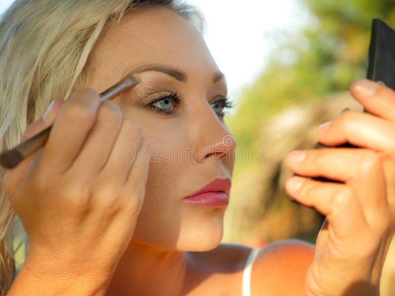 有蓝眼睛的年轻美丽和可爱的白肤金发的妇女修饰与刷子的构成描出拿着小镜子的眼眉  图库摄影