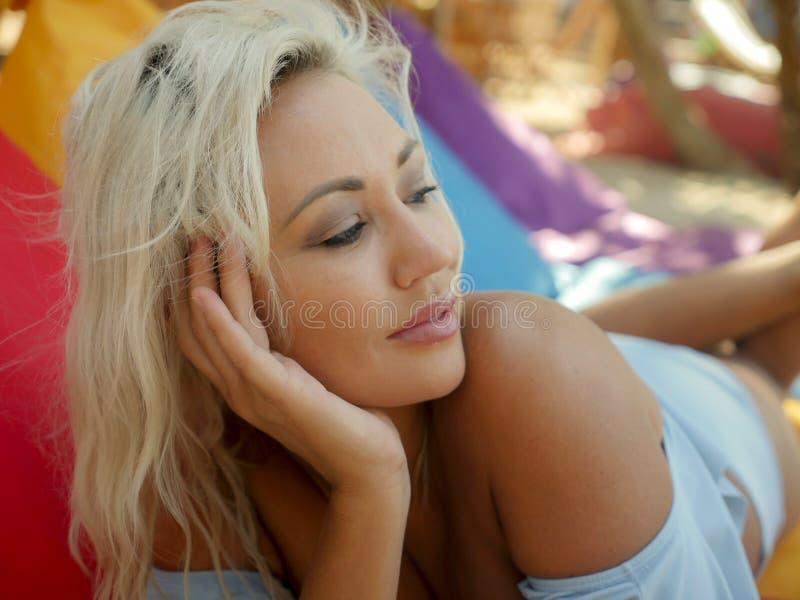 有蓝眼睛的年轻美丽和愉快的白肤金发的妇女放松了并且使说谎在装豆子小布袋吊床变冷在太阳佩带时髦下 免版税图库摄影