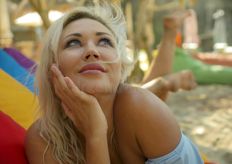 有蓝眼睛的年轻美丽和愉快的白肤金发的妇女放松了并且使说谎在装豆子小布袋吊床变冷在太阳佩带时髦下 免版税库存照片