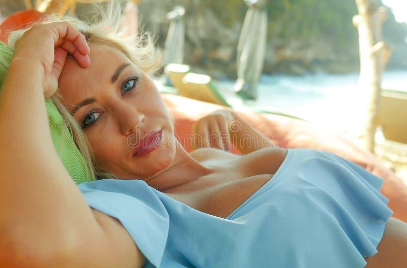 有蓝眼睛的年轻美丽和愉快的白肤金发的妇女放松了并且使说谎在装豆子小布袋吊床变冷在太阳佩带时髦下 免版税库存图片