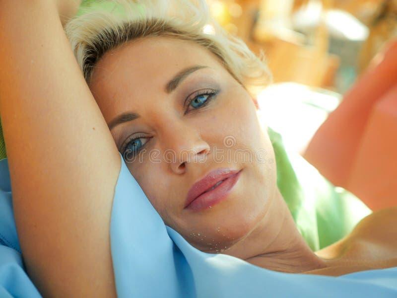有蓝眼睛的年轻美丽和愉快的白肤金发的妇女放松了并且使说谎在装豆子小布袋吊床变冷在太阳佩带时髦下 库存照片