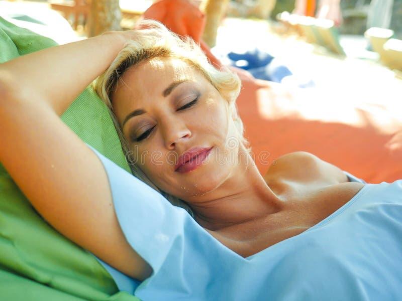 有蓝眼睛的年轻美丽和愉快的白肤金发的妇女放松了并且使说谎在装豆子小布袋吊床变冷在太阳佩带时髦下 图库摄影