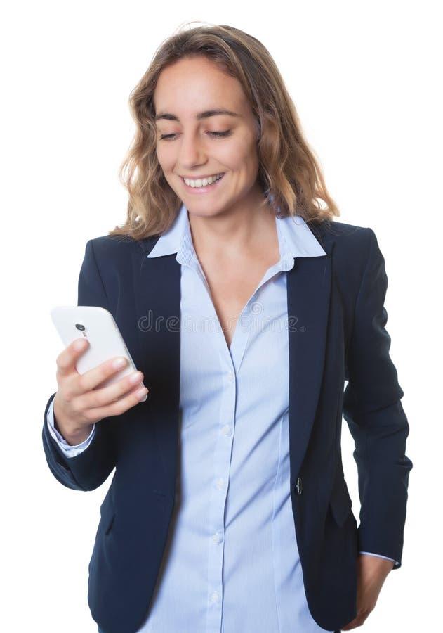 有蓝眼睛的白肤金发的传送与电话的女实业家和燃烧物信息 免版税库存照片