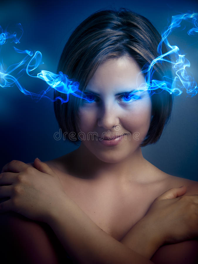有蓝眼睛的美丽的少妇,从h出来的蓝色烟 库存图片