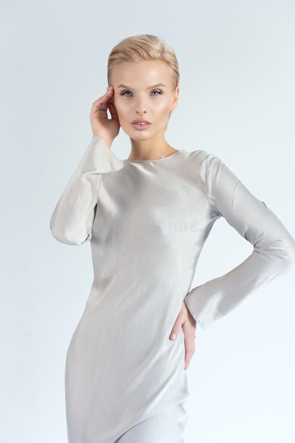 有蓝眼睛的美丽的性感的白肤金发的女孩在银色丝绸礼服 库存图片