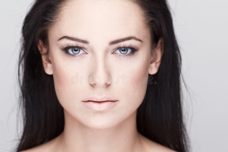 有蓝眼睛的美丽的深色的妇女 库存照片