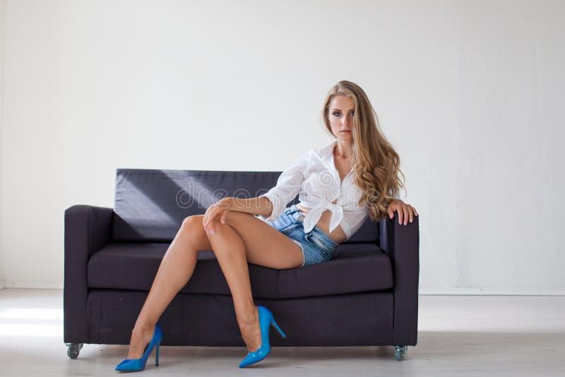 有蓝眼睛的美丽的白肤金发的女孩坐长沙发在一个绝尘室1 免版税库存图片