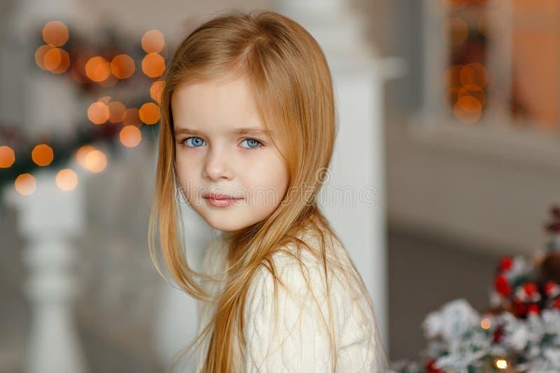 有蓝眼睛的美丽的矮小的白肤金发的女孩微笑在新的Ye的 免版税库存照片