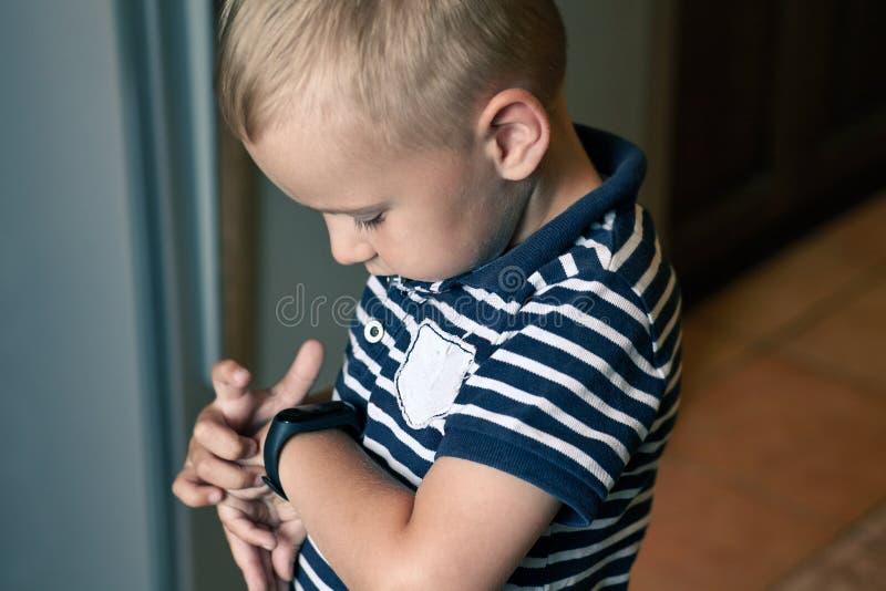 有蓝眼睛的逗人喜爱的矮小的白肤金发的男孩指出给他的腕子的数字健身跟踪仪 免版税库存照片