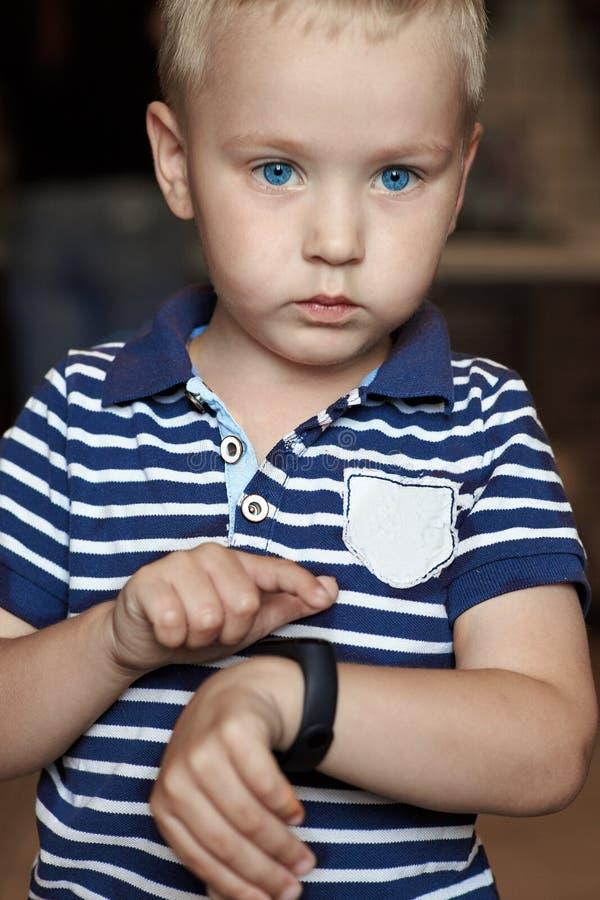 有蓝眼睛的逗人喜爱的矮小的白肤金发的男孩指出给他的腕子的数字健身跟踪仪 免版税库存图片