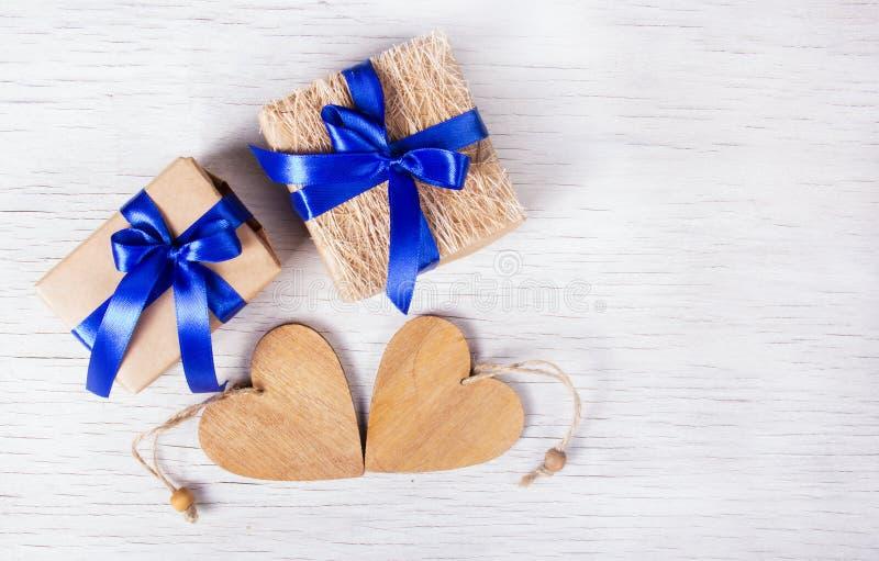 有蓝色丝带的两个礼物盒和在白色背景的木心脏 日s华伦泰 复制空间 图库摄影