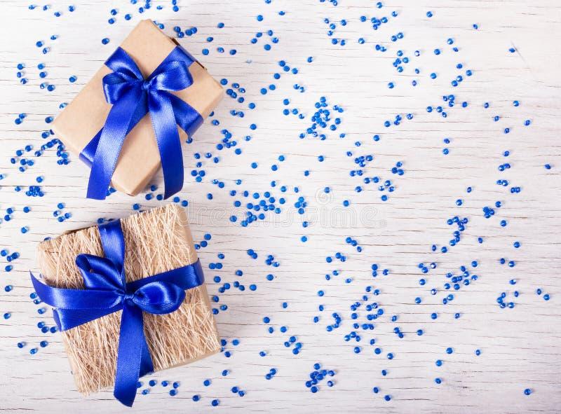 有蓝色丝带的两个礼物盒在与闪闪发光的白色背景 复制空间 图库摄影