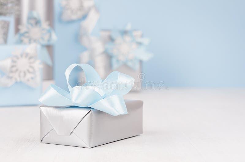 有蓝色丝绸弓特写镜头的欢乐银色金属礼物盒和另外在背景的高雅软的圣诞礼物在迷离 库存照片