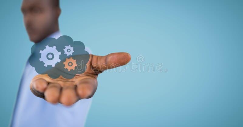 有蓝色云彩和齿轮图表的商人在反对蓝色背景的被伸出的手上 免版税图库摄影